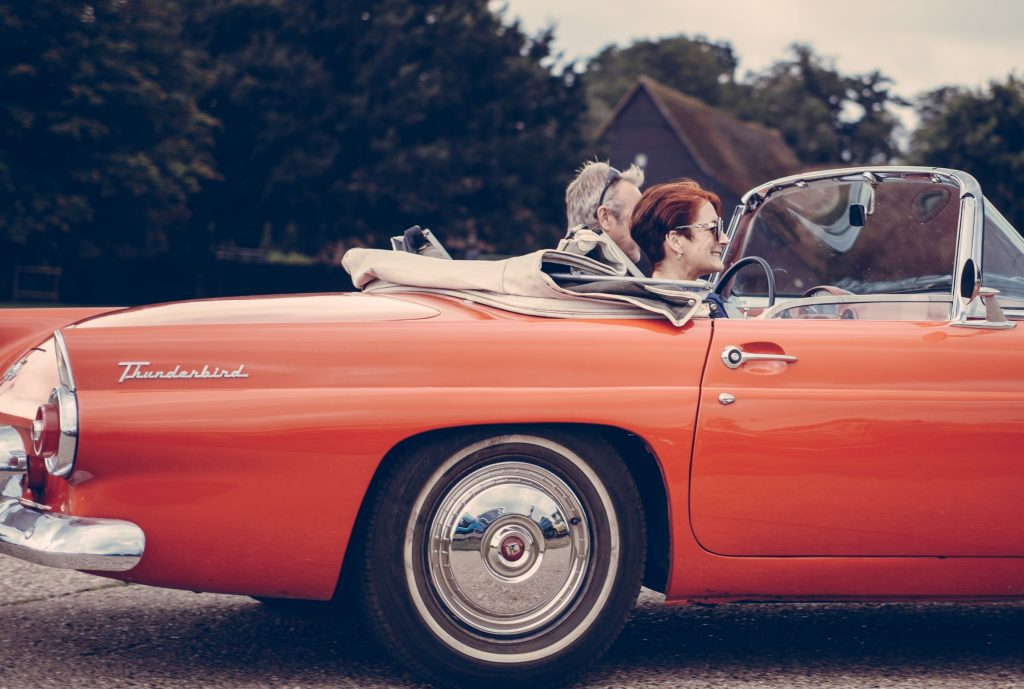 couple riding in flame orange Tbird convertible, top down