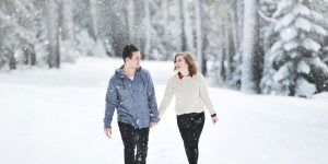 male female couple holding hands walking throw snowflakes