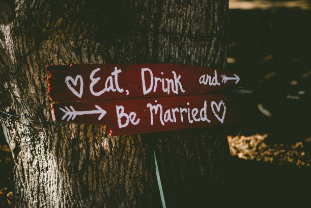 Eat, Drink and Be Married sign with hearts and arrows leaning against tree, premarital counseling before your wedding