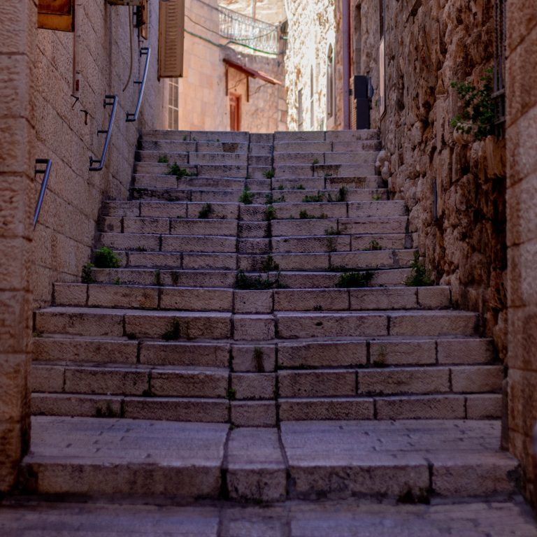 stone stairway between buildings going up from this view, light at the end
