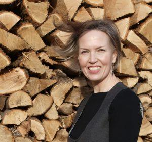 JoEllen hair blowing, wood pile behind